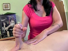 Dark haired woman is rubbing a rock hard cock while her partner is moaning from pleasure
